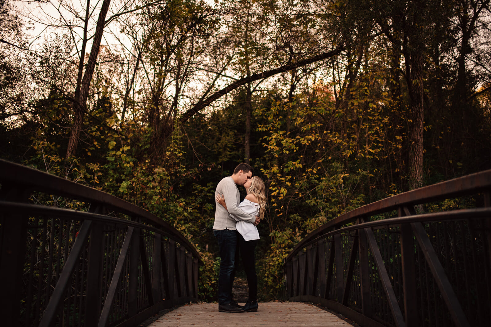 couple kisses on bridge in conservation area