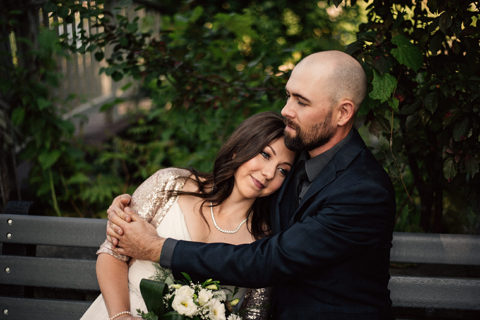 bride and groom cuddle on park bench
