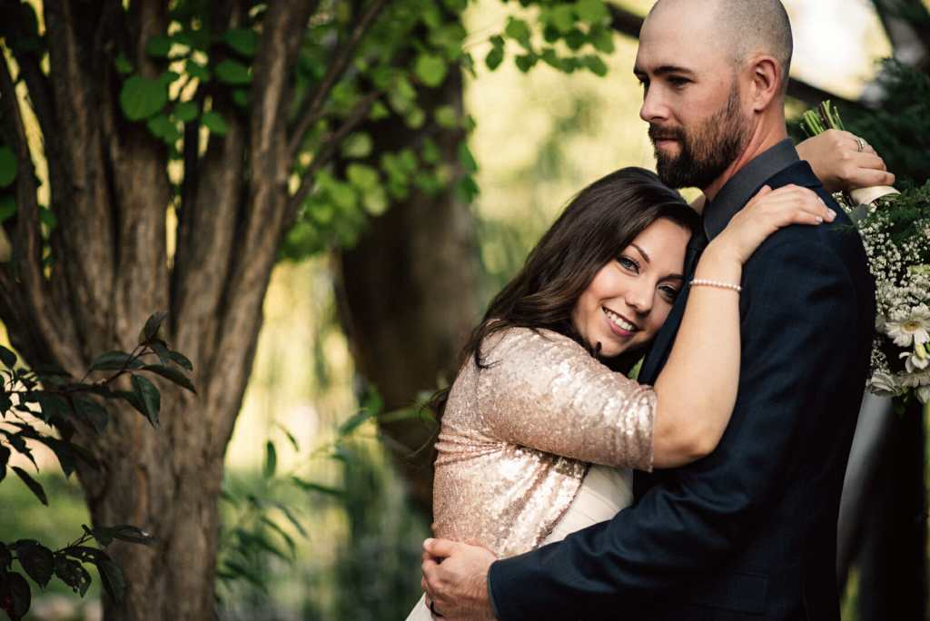 bride and groom cuddle during wedding photos