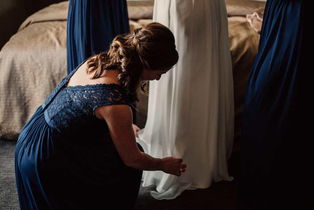 bridesmaid helps bride get ready