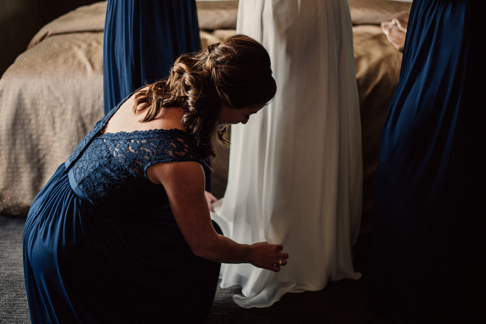 bridesmaid helps bride get ready