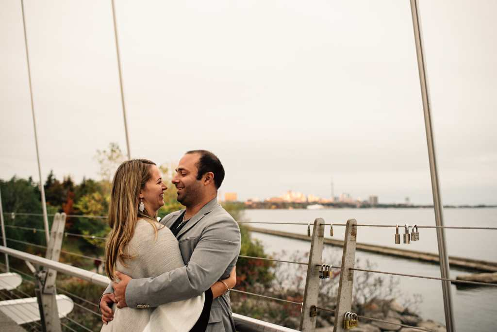 couple laugh together on bridge