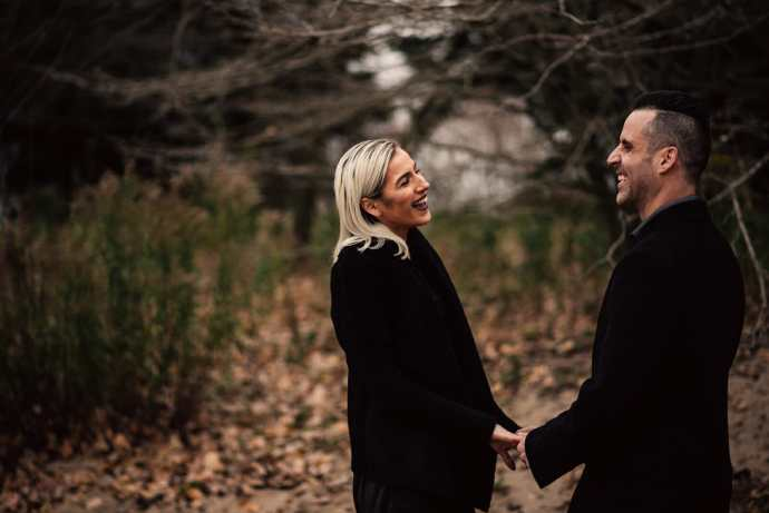 boyfriend and girlfriend hold hands and laugh in forest