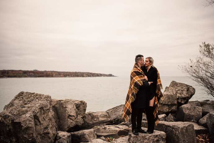 man and women cuddle up under a blanket on rocks by lake ontario