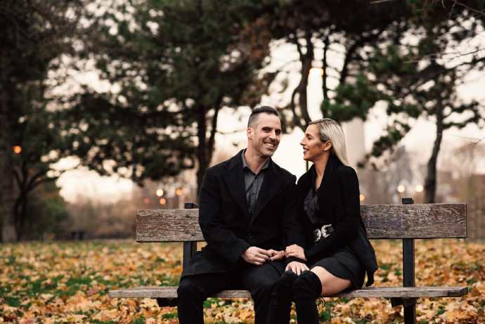 engaged couple smiles on bench surrounded by fall leaves