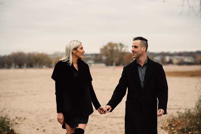 newly engaged couple walks in sand at toronto beach