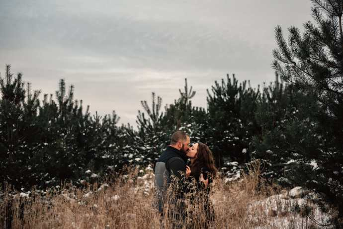 fiance kisses his fiancee surrounded by tall grass and pine trees