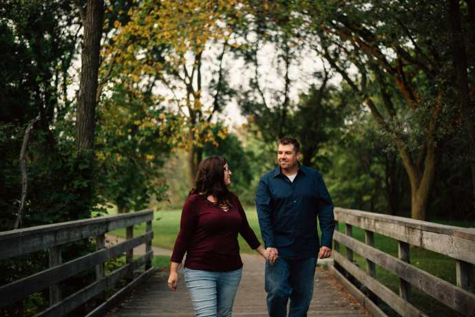 couple walk hand in hand over bridge in forest
