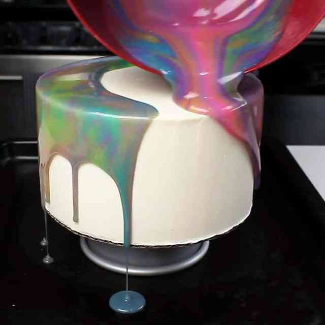 Pouring mirror glaze over chilled buttercream cake