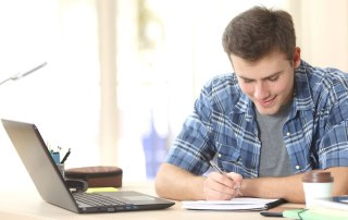 Boy taking notes whilst working with online tutor