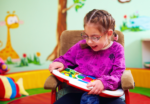cute girl in wheelchair playing with developing toy in kindergarten for children with special needs