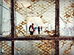 """A view through broken glass into the """"Trace"""" exhibit of Lego portraits, in the New Industries Building."""