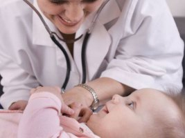 Doctor with stethoscope listening to baby's heart at CHC