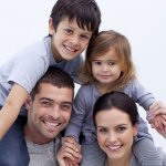 Photo of a happy family with their children and their shoulders posing for a picture at cherubino health center
