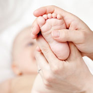 Baby with doctors hand on her foot