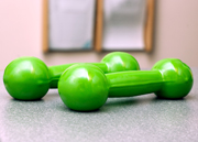 Green rubberized Dumbells on a table