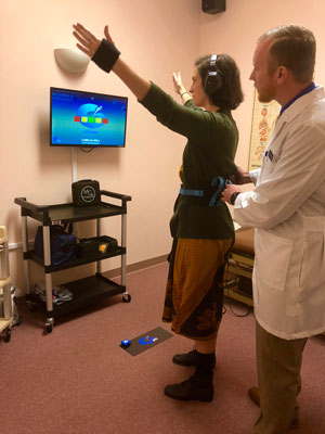 Dr Lars Landers helping a patient perform Interactive Metronome at Cherubino Health Center