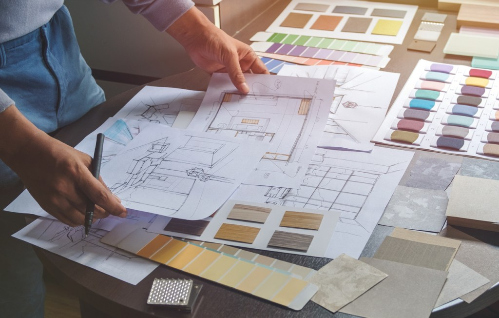hands-of-architect-holding-blueprints-of-home-on-desk-with-paint-and-material-swatches