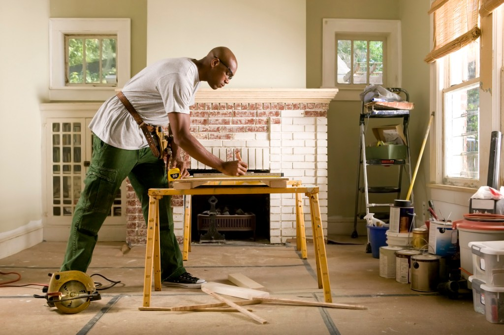 man-standing-at-sawhorse-marking-wood-with-pencil-in-room-being-renovated