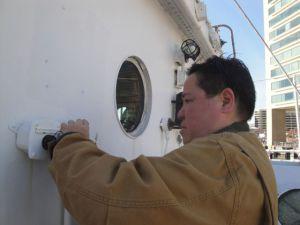 Photo by Anne Puppa Susan Duke wraps wiring in bracket on deck.