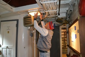 Tall Tony Pasek fixes light in ships mess.