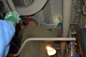 Tony working on brackets for electrical wires in engine room.