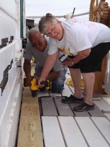 Cathy and Howard Lewis replacing deck board near hatch.