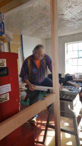 Virgil Ramey works on doorframe repair.