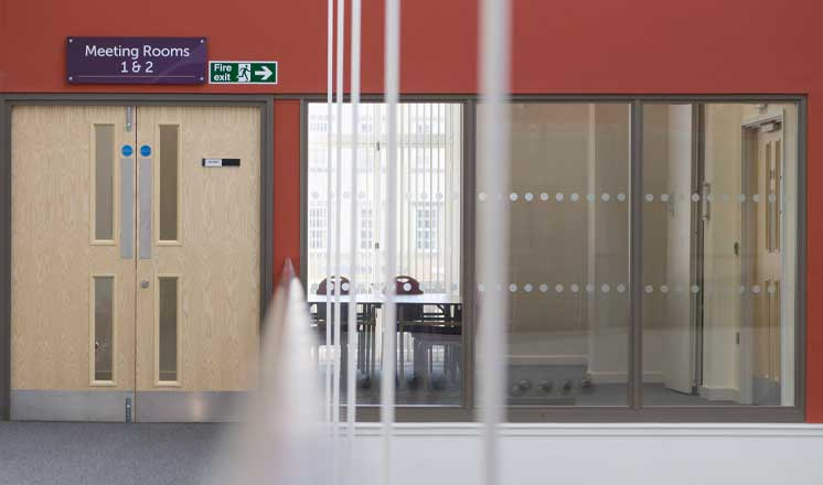 The entrance to Meeting Rooms 1 and 2 at the Assembly Rooms, with a large glass window showing meeting tables set up.