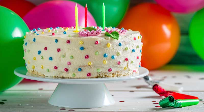 A birthday cake covered in multicoloured sprinkles with candles. Balloons and party streamers are on the table behind.