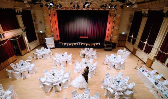 The Winding Wheel auditorium set up for a wedding reception, a bride and groom dancing in the centre.
