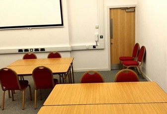Meeting Room 1 at the Assembly Rooms set up with several tables of four.