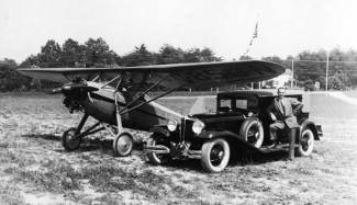 """Chet with his two loves and livelihoods, the airplane and the car. Photo taken at Congressional Airport in May 1930. The plane is a Davis D-1; Chet was a Davis dealer as well as a Stinson one, and he took his pilot's licence test in a Davis. His Davis """"lot"""" was at Congressional."""