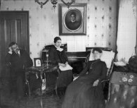 At home in Chicago: from right to left, George, his mother Isabella MacArthur Warrington, and Minnie. All of them are under the watchful gaze of Isabella's magnificent Victorian portrait. Scanned directly from the glass negative.