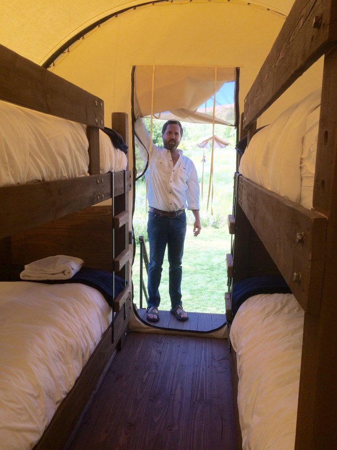 Tom Hedges, one of the owners of the Conestoga Ranch, shows the sets of bunk beds in a covered wagon, Bear Lake, Utah.