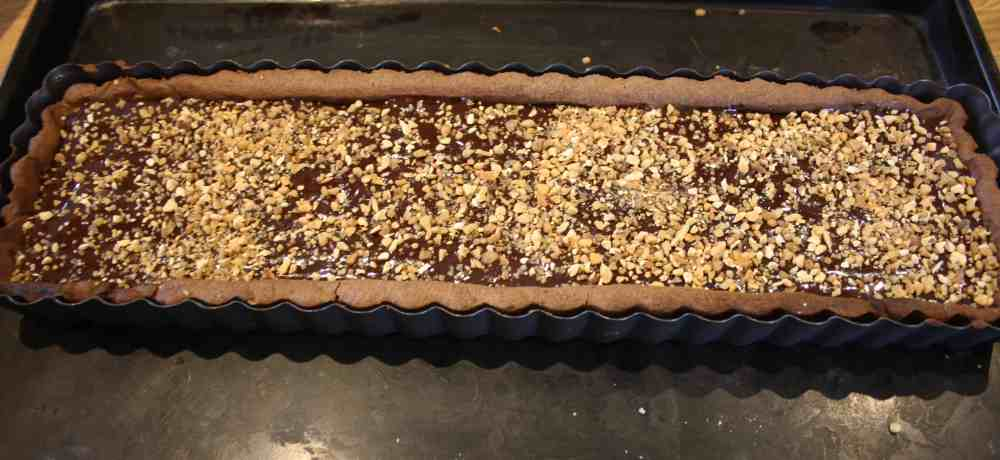 Caramel Chocolate Tart. Homemade caramel oozes over a crisp chocolate pastry base and is finished with a baked chocolate topping.