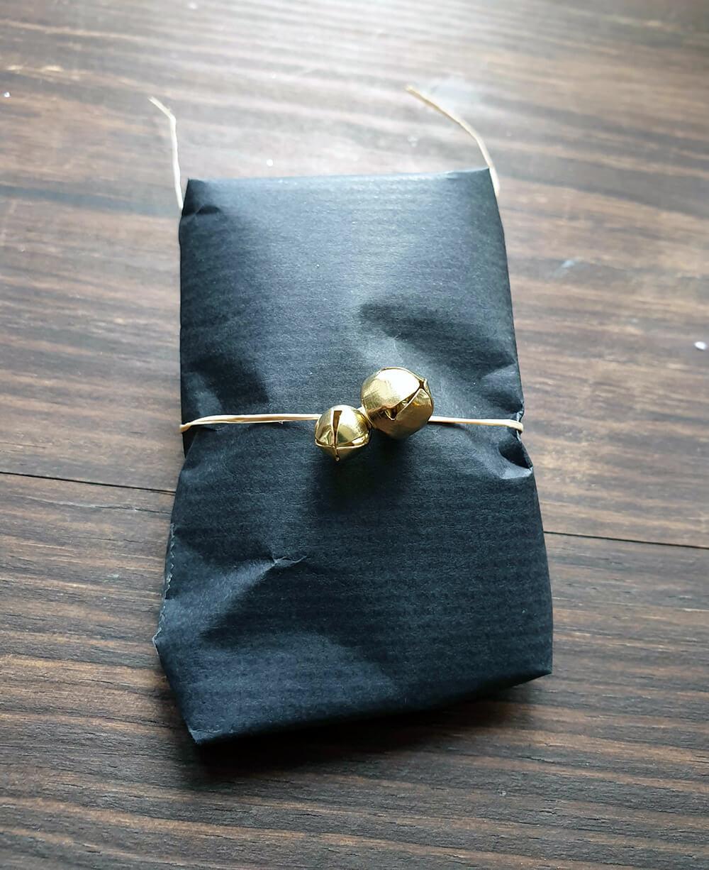 petit cadeau de noel emballé avec du papier kraft noir de la ficelle et des grelots - 7 idées d'emballage cadeau zéro déchet faciles à reproduire