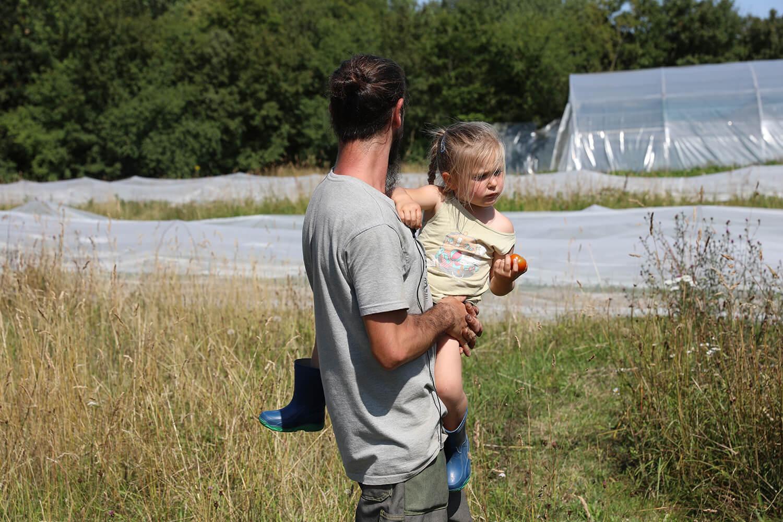 Jimmy regardant son champs avec son enfant dans les bras - Potage et Nature : une ode à la permaculture au coeur de la Bretagne