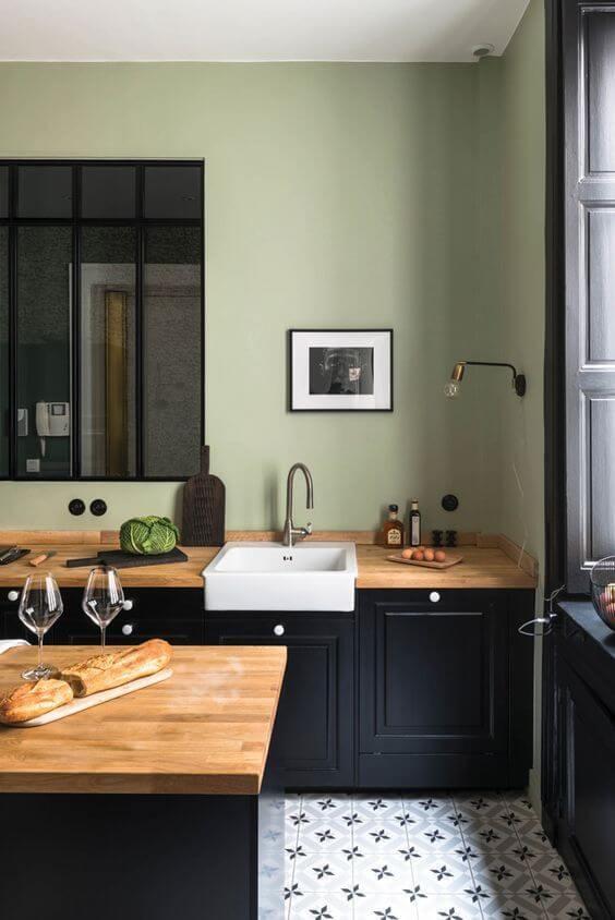cuisine mur vert sol carreaux de ciment et meuble noir avec plan de travail bois - L'irrésistible cuisine noire : une inspiration moderne et tendance