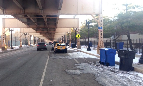 Garbage bins are stored in the Lake Street protected bike lane, atop snow piles.