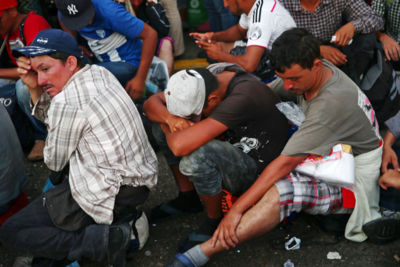 Central American migrants, part of a caravan trying to reach the U.S., wait on the bridge that connects Mexico and Guatemala to cross into Mexico to continue their trip, in Ciudad Hidalgo