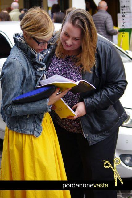 Il gonnellone e il giubbetto in jeans con voile sono i capi selezionati da questa lettrice intenta a sfogliare il programma della 18esima edizione con l'amica.