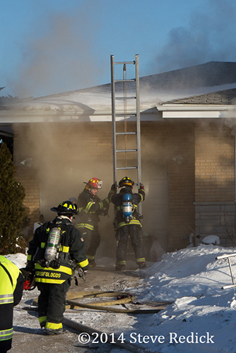 firemen place ladder at house fire