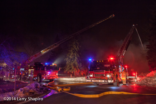 two aerial ladder trucks at night fire scene with master streams