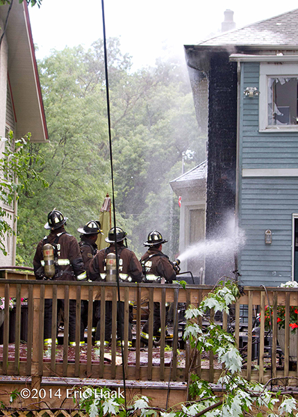 firemen with hoseline at fire scene