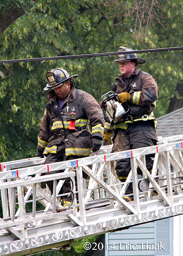 firemen with saw on E-ONE aerial ladder