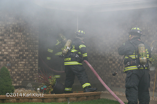 firemen entering house with hose line and heavy smoke