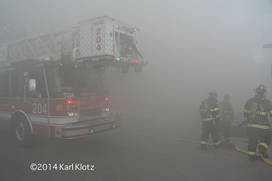thick smoke engulfs firemen and fire truck