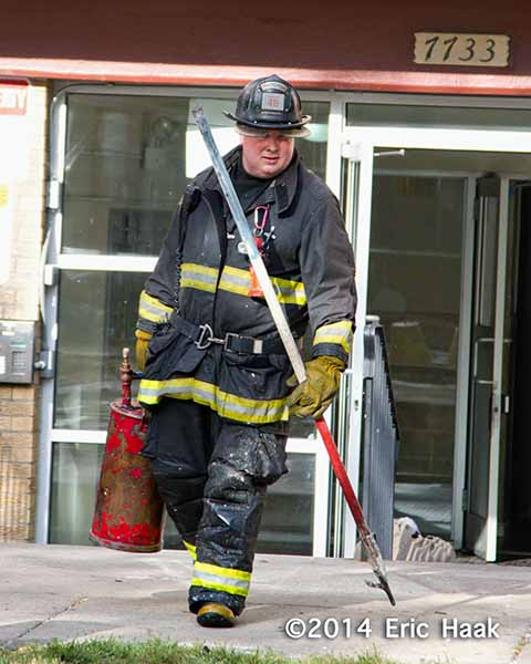 fireman carries tools after fire