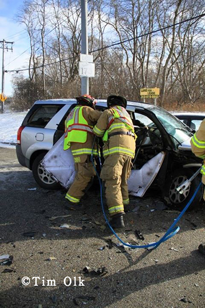 firemen cut victim from car after crash